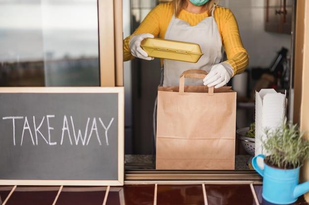Jovem mulher preparando comida orgânica para viagem dentro de restaurante