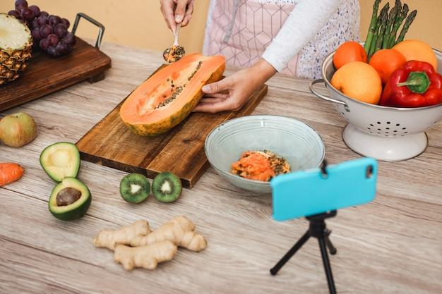Jovem mulher preparando salada saudável durante o streaming on-line para aula de webinar - garota influenciadora fazendo smoothie fazendo masterclass de vídeo com câmera de telefone durante a quarentena de isolamento - concentre-se na mão direita