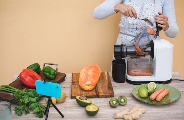 Jovem mulher preparando suco orgânico com máquina extrator prensado a frio - garota fazendo smoothie com legumes e frutas