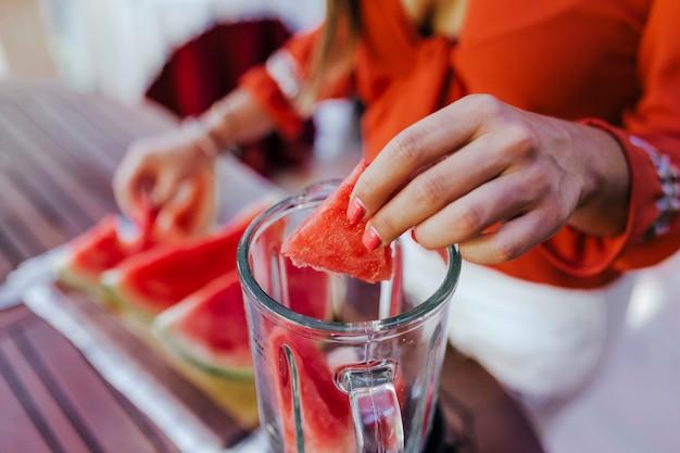 Jovem mulher preparando uma receita saudável de diversas frutas, melancia, laranja e amoras. usando um misturador. estilo de vida caseiro, caseiro e saudável