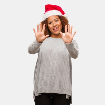 Jovem, mulher preta, desgastar, um, chapéu santa, mostrando, numere dez