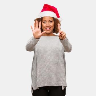Jovem, mulher preta, desgastar, um, chapéu santa, mostrando, numere seis
