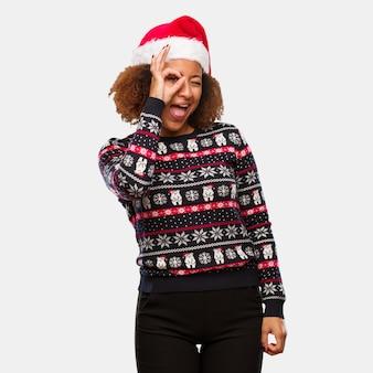 Jovem, mulher preta, em, um, trendy, natal, suéter, com, impressão, confiante, fazendo, ok, gesto, ligado, olho