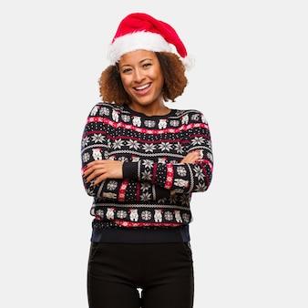 Jovem, mulher preta, em, um, trendy, natal, suéter, com, impressão, cruzamento, braços, sorrindo, e, relaxado
