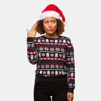 Jovem, mulher preta, em, um, trendy, natal, suéter, com, impressão, fazendo, um, gesto suicídio