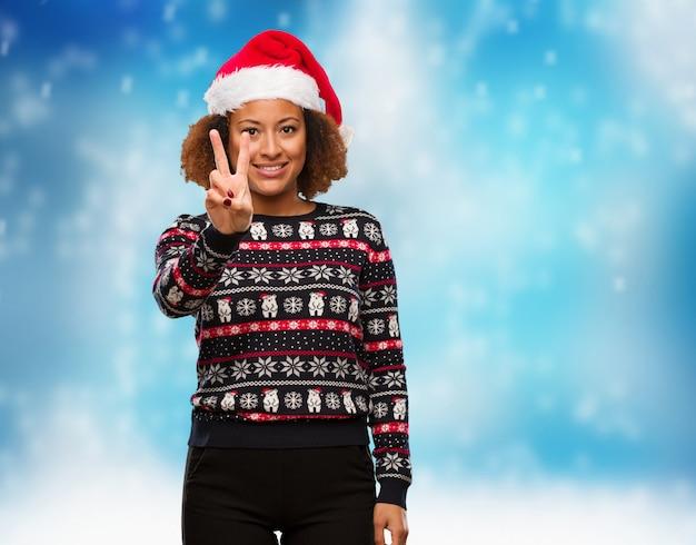 Jovem, mulher preta, em, um, trendy, natal, suéter, com, impressão, mostrando, numere dois