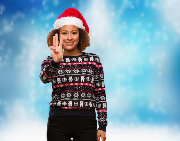 Jovem, mulher preta, em, um, trendy, natal, suéter, com, impressão, mostrando, numere três