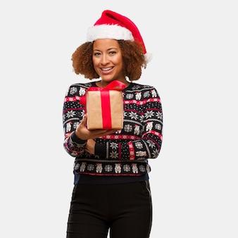 Jovem, mulher preta, segurando, um, presente, em, dia christmas, cruzamento, braços, sorrindo, e, relaxado