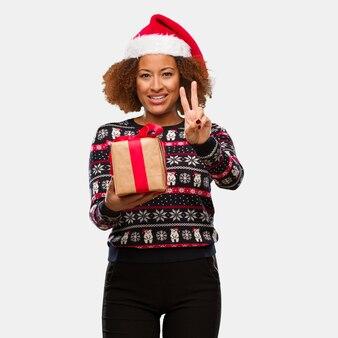 Jovem, mulher preta, segurando, um, presente, em, dia natal, mostrando, numere dois
