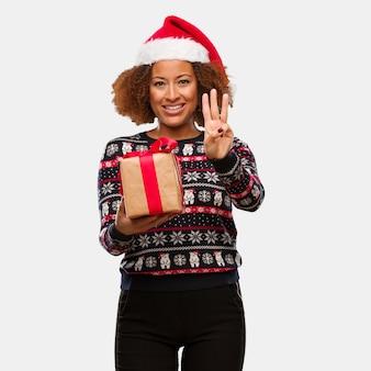 Jovem, mulher preta, segurando, um, presente, em, dia natal, mostrando, numere três