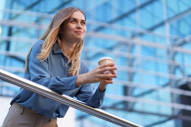 Jovem mulher profissional sorridente, fazendo uma pausa para o café durante seu dia inteiro de trabalho. ela segura um copo de papel ao ar livre perto do prédio comercial, enquanto relaxa e aprecia sua bebida.
