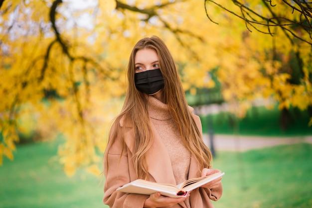 Jovem mulher protegendo do vírus corona ao caminhar no parque. fundo de outono.