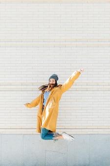 Jovem mulher pulando contra parede de tijolos usando fone de ouvido