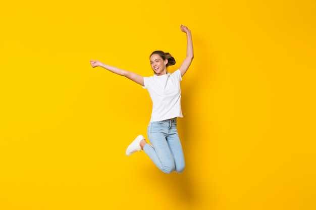 Jovem mulher pulando parede amarela isolada