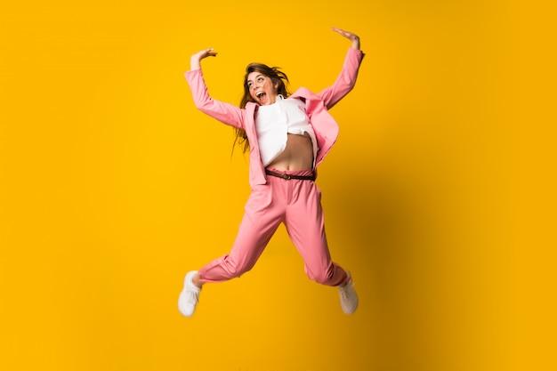 Jovem, mulher, pular, isolado, amarela, parede, fazer, vitória, gesto