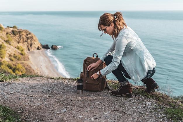Jovem mulher quadril olhando em sua mochila explora a costa em um lindo dia. conceito de exploração e aventuras