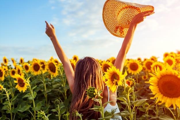 Jovem mulher que anda no campo de florescência do girassol que levanta as mãos, saltando e tendo o divertimento.