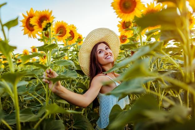 Jovem mulher que anda no campo de florescência do girassol que sente livre e que admira a natureza.