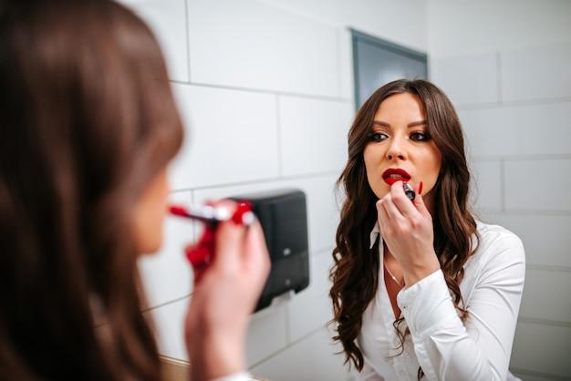 Jovem mulher que aplica o batom vermelho ao olhar o espelho.