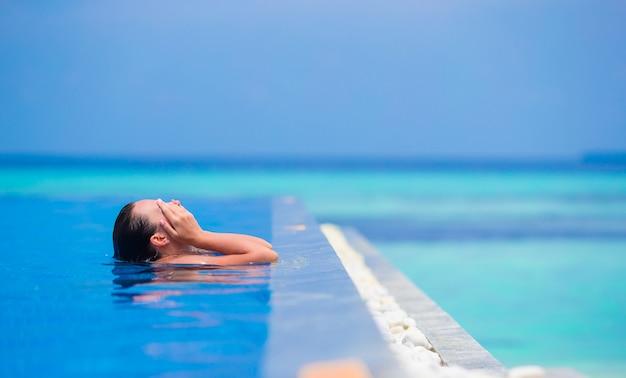 Jovem mulher que aprecia a água e o sol na piscina exterior.