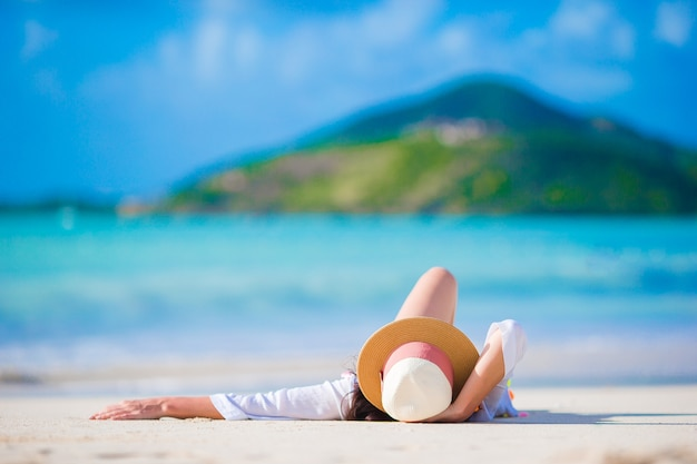 Jovem mulher que aprecia o sol que sunbathing pelo oceano perfeito de turquesa.