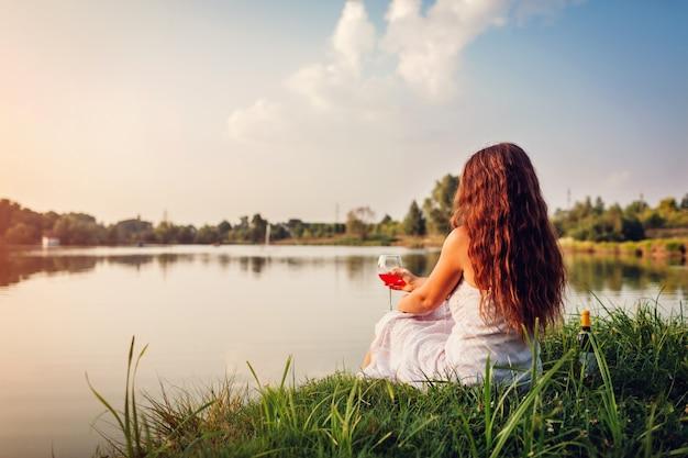 Jovem mulher que aprecia o vidro do vinho no banco de rio no por do sol. mulher, admirar, paisagem, tendo, bebida