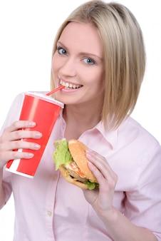 Jovem mulher que come o fast food e que bebe a soda.