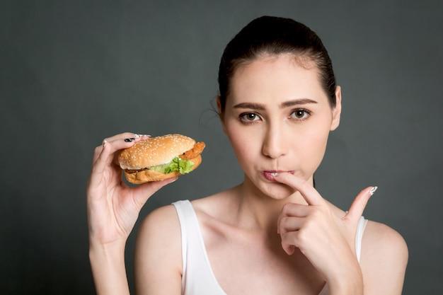 Jovem mulher que come o hamburger no fundo cinzento. junk food e conceito de fast food
