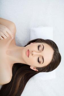 Jovem mulher que encontra-se em uma tabela da massagem, relaxando com os olhos fechados. mulher. salão spa