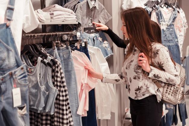 Jovem mulher que escolhe a roupa em uma cremalheira em uma sala de exposições.