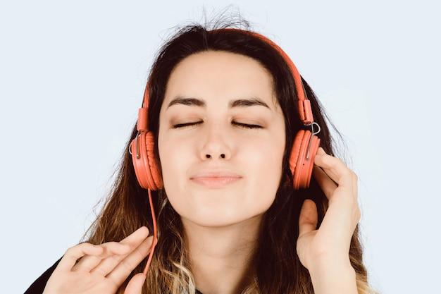 Jovem mulher que escuta a música no estúdio.