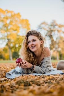Jovem mulher que estabelece na terra no parque do outono.