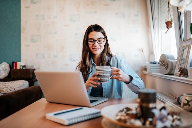Jovem mulher que estuda e que bebe o café em seu apartamento.
