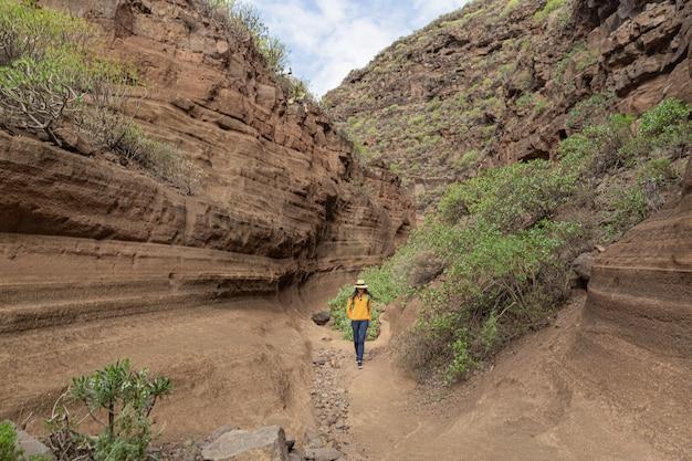 Jovem mulher que explora barranco de las vacas, gran canaria, espanha das ilhas canárias. geologia, paisagem vulcânica e conceito de férias.