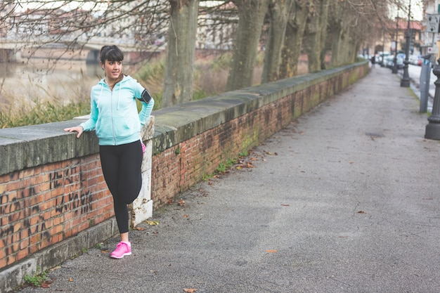 Jovem mulher que faz esticando exercícios antes de movimentar-se.