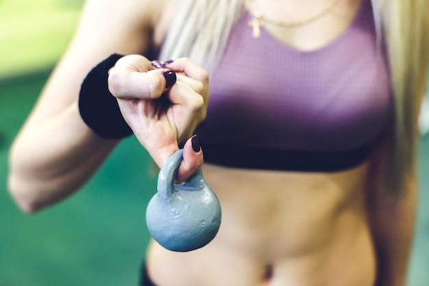 Jovem mulher que faz exercícios com pesos em um gym. dedo segurando o close-up do peso.