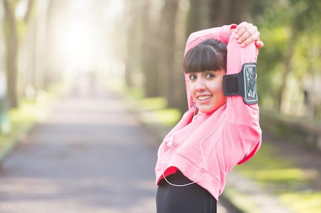 Jovem mulher que faz os braços e os ombros que esticam exercícios.