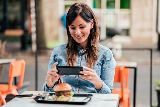 Jovem mulher que fotografa o hamburguer delicioso no restaurante de fastfood fora.
