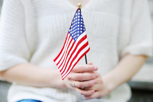 Jovem mulher que guarda a bandeira americana conceito do dia da independência.