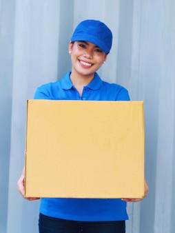 Jovem mulher que guarda a caixa para entregar ao cliente.