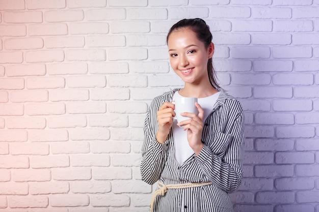 Jovem mulher que guarda a xícara de café no fundo da parede de tijolo