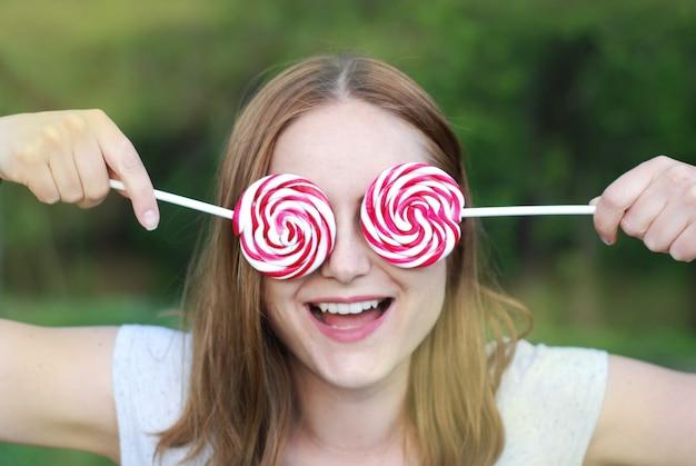 Jovem mulher que guarda dois doces do pirulito. se divertindo.