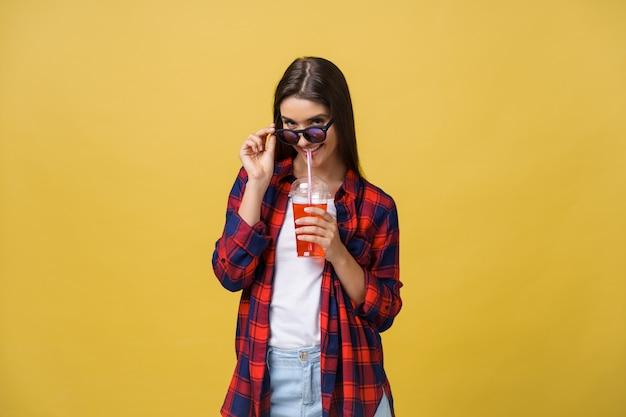 Jovem mulher que guarda e que bebe a bebida fria da bebida na roupa ocasional.