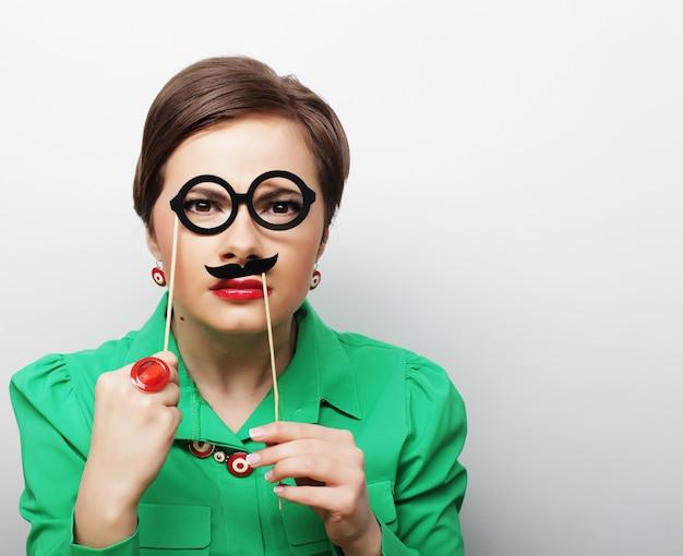 Jovem mulher que guarda o bigode e os vidros em uma vara.