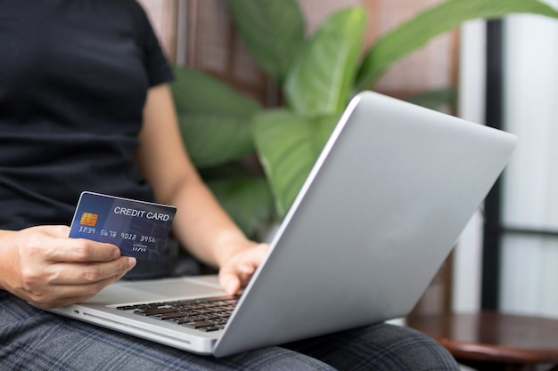 Jovem mulher que guarda o cartão de crédito e que usa o laptop. conceito de compras online. copie o espaço.