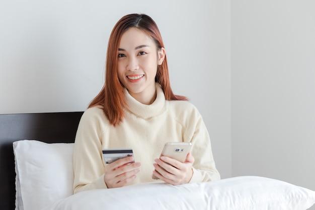 Jovem mulher que guarda o cartão de crédito e que usa o telefone celular. conceito de compras on-line
