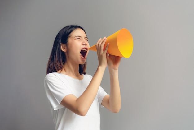 Jovem mulher que guarda o megafone de papel e que grita em.