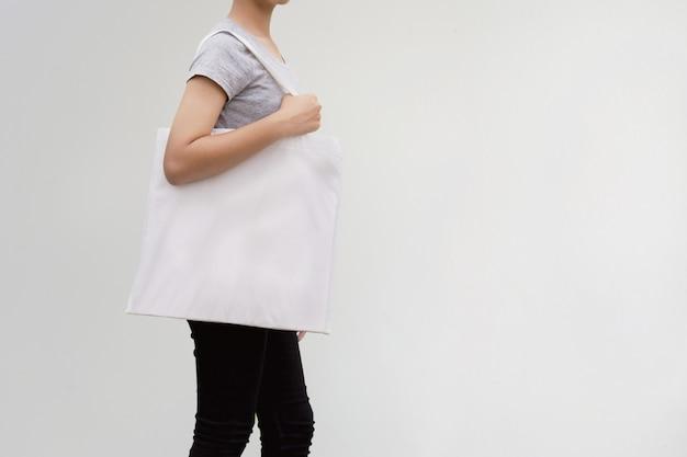 Jovem mulher que guarda o saco do algodão no fundo da parede. conceito eco