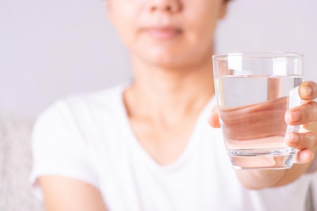 Jovem mulher que guarda o vidro de água potável em sua mão. conceito de cuidados de sa