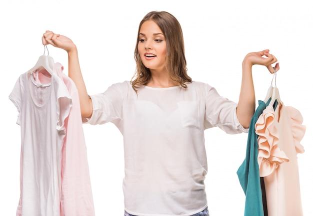 Jovem mulher que guarda seus vestidos novos